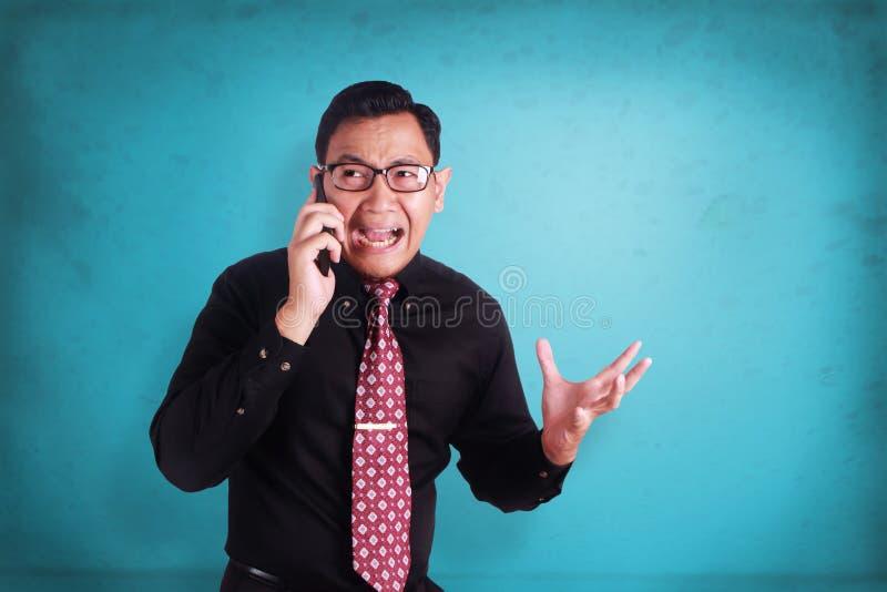 可爱的年轻商人谈话在他的电话,震惊cryin 库存照片