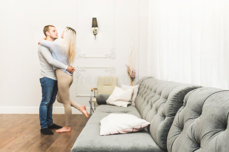 可爱的年轻夫妇在有一现代内部面对面的一个客厅 免版税图库摄影