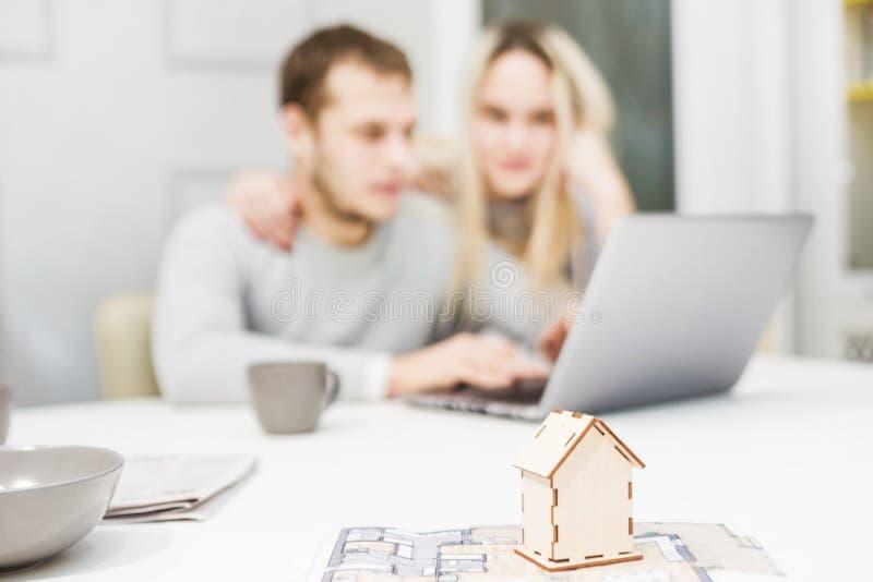 可爱的年轻夫妇,使用膝上型计算机和选择一栋新的公寓 房子的布局前景的 免版税库存图片
