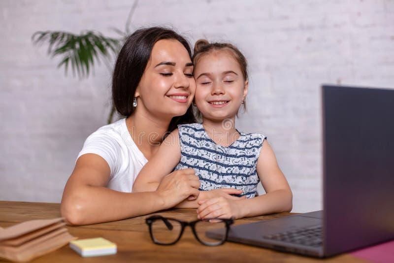 可爱的年轻女人和她的小逗人喜爱的女儿坐在桌上并且获得乐趣,当做家庭作业时 库存图片