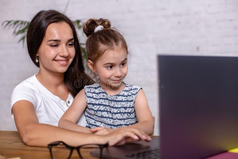 可爱的年轻女人和她的小逗人喜爱的女儿坐在桌上并且获得乐趣,当做家庭作业时 免版税库存照片