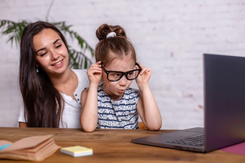 可爱的年轻女人和她的小逗人喜爱的女儿坐在桌上并且获得乐趣,当做家庭作业时 库存照片