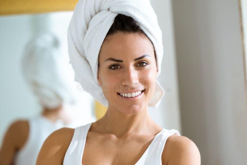 可爱的年轻女人在头附近在家包裹了一块毛巾在她的卫生间里 图库摄影