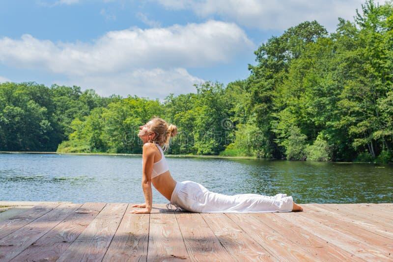 可爱的年轻女人实践瑜伽,做眼镜蛇姿势在湖附近 免版税库存照片