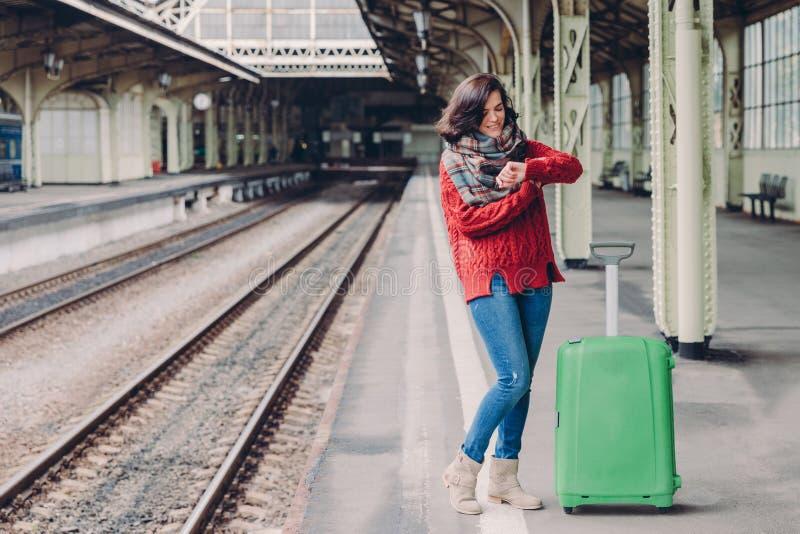 可爱的年轻女人照片等待火车在火车站,穿戴在被编织的毛线衣,并且牛仔裤,在绿色袋子附近的立场,看 免版税库存照片