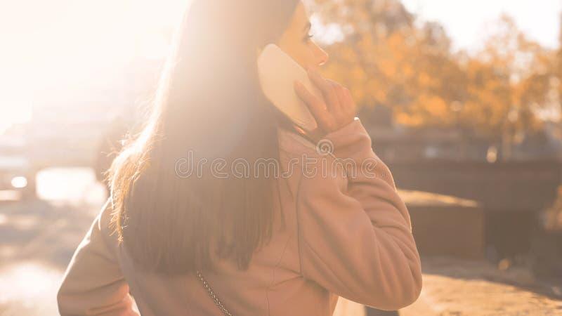 可爱的年轻女人谈话在告诉的智能手机朋友,有利关税 库存图片