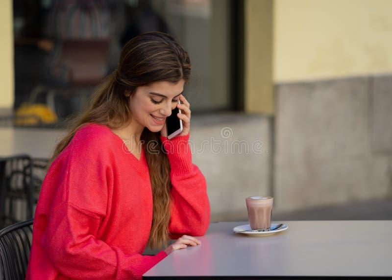可爱的年轻女人谈话在她在咖啡馆大阳台的巧妙的手机 免版税库存照片