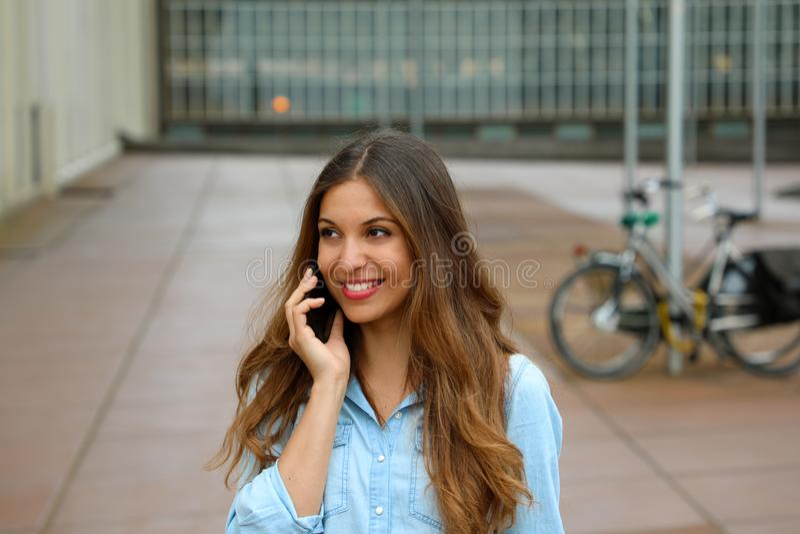 可爱的年轻女商人谈话在她的电话,当站立在办公大楼时庭院里  室外快乐的女商人 免版税库存照片