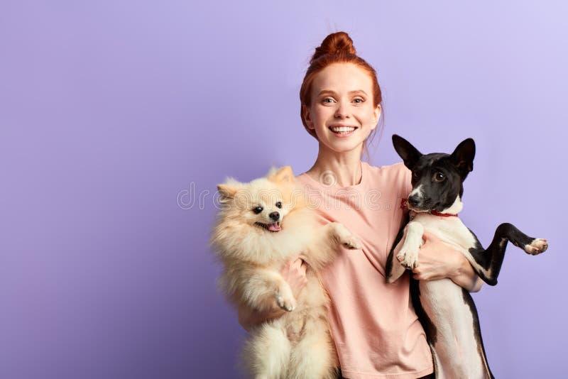 可爱的年轻微笑的姜妇女拥抱她的狗 免版税库存图片