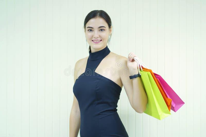 可爱的年轻愉快的微笑的妇女画象有购物带来的 库存照片