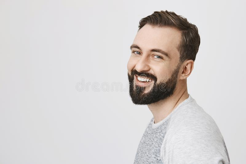 可爱的年轻成人人画象有胡子和髭的移交了照相机,表示高兴,当站立时 图库摄影