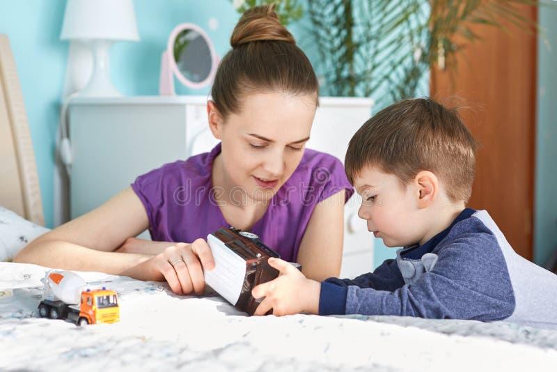可爱的年轻母亲画象使用与小男性kis,告诉他事有趣关于玩具汽车,姿势一起反对是 库存图片
