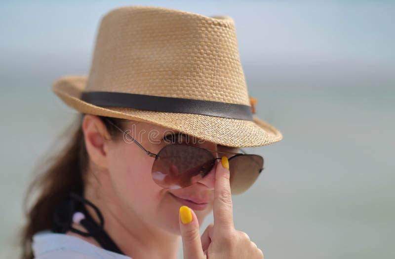 可爱的年轻深色的妇女调直在她的面孔,性感的神色的太阳镜,调查照相机 免版税库存照片