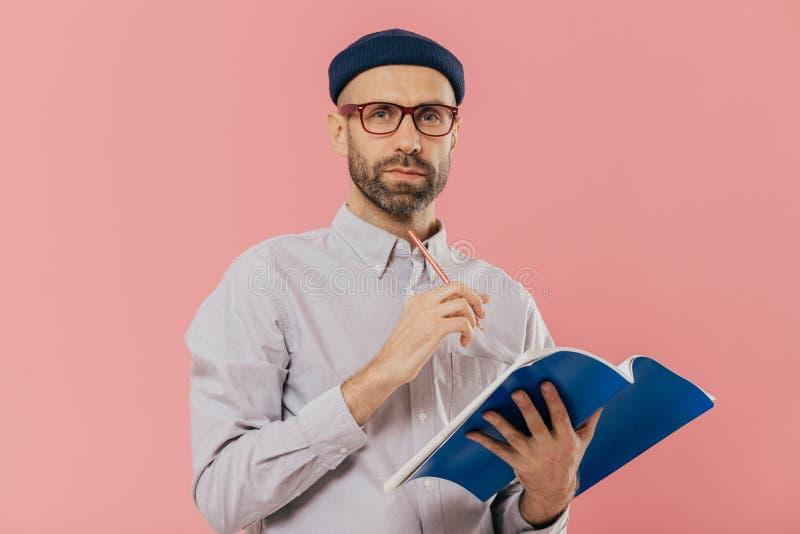 可爱的年轻男性射击拿着课本,做在组织者的笔记,正式地打扮 聪明的学生为做准备 库存图片