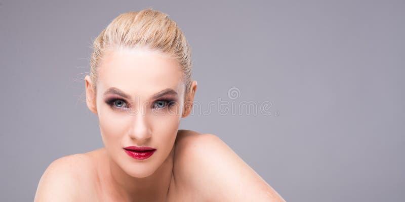 可爱的年轻白肤金发的妇女佩带的魅力构成 免版税库存照片