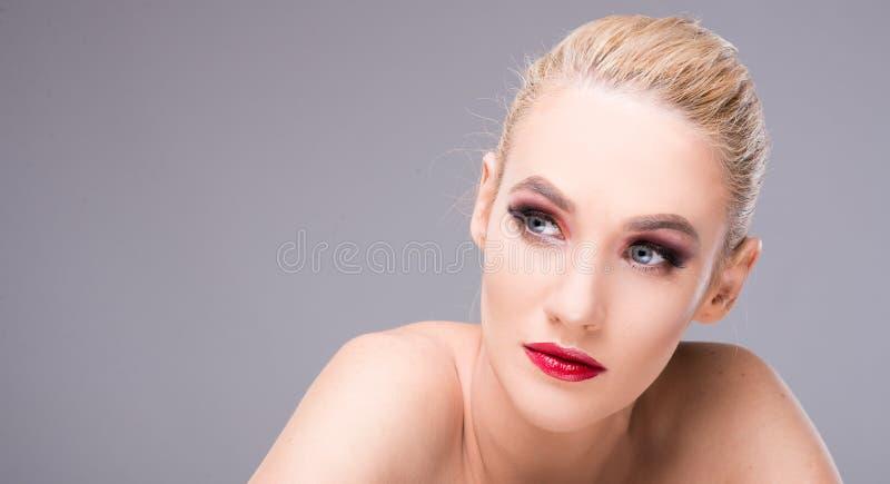 可爱的年轻白肤金发的妇女佩带的魅力构成 图库摄影