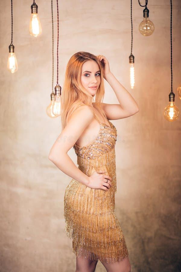 可爱的年轻白肤金发的妇女美丽的画象短的典雅的金黄礼服的在有明亮的黄色灯的演播室 党, 免版税库存照片