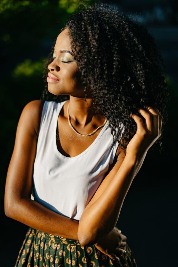 可爱的年轻美国黑人的女孩的半身画象有嫉妒的遮蔽接触她长的黑暗的卷发 免版税图库摄影