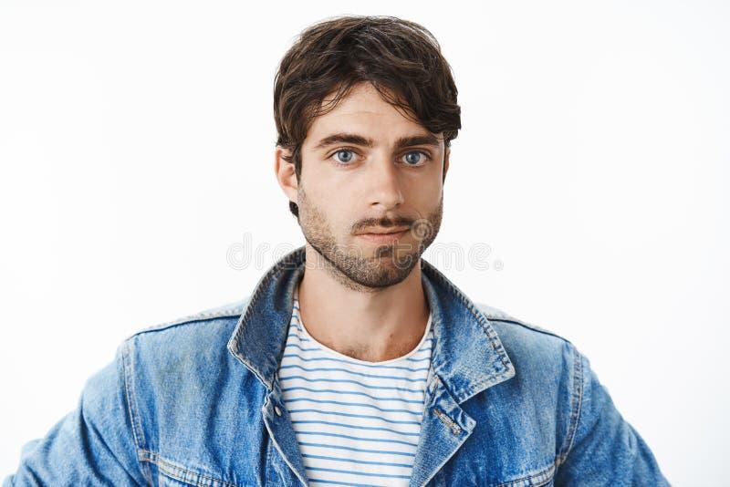 可爱的年轻西班牙在牛仔布夹克的人和胡子特写有蓝眼睛的在看的镶边T恤杉 免版税库存图片