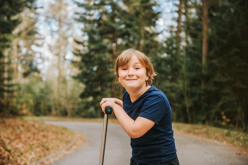 可爱的年轻8岁画象倾斜在他的滑行车的白肤金发的男孩 免版税库存图片