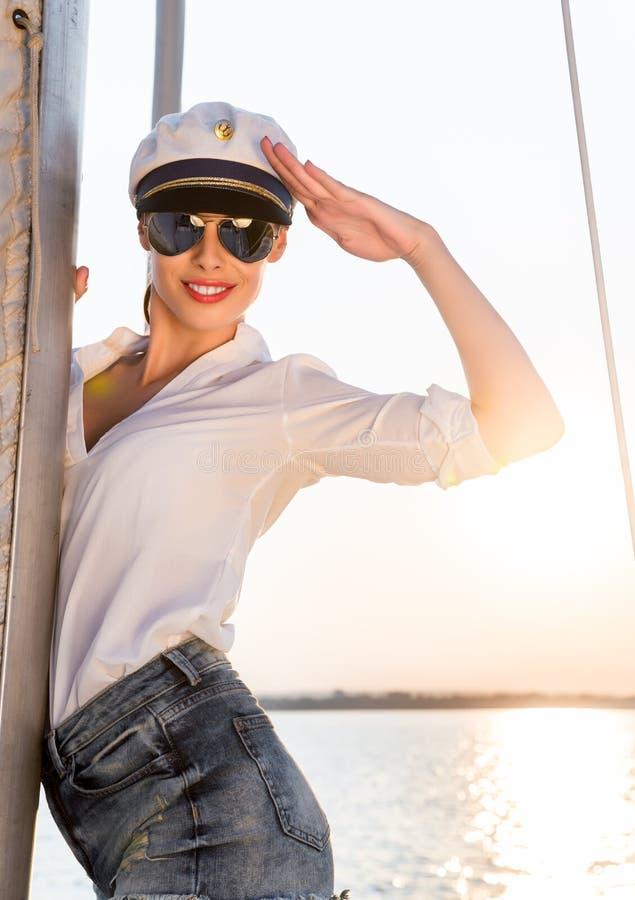 可爱的式样佩带的海海军上将帽子和性感的上面在日落 免版税图库摄影