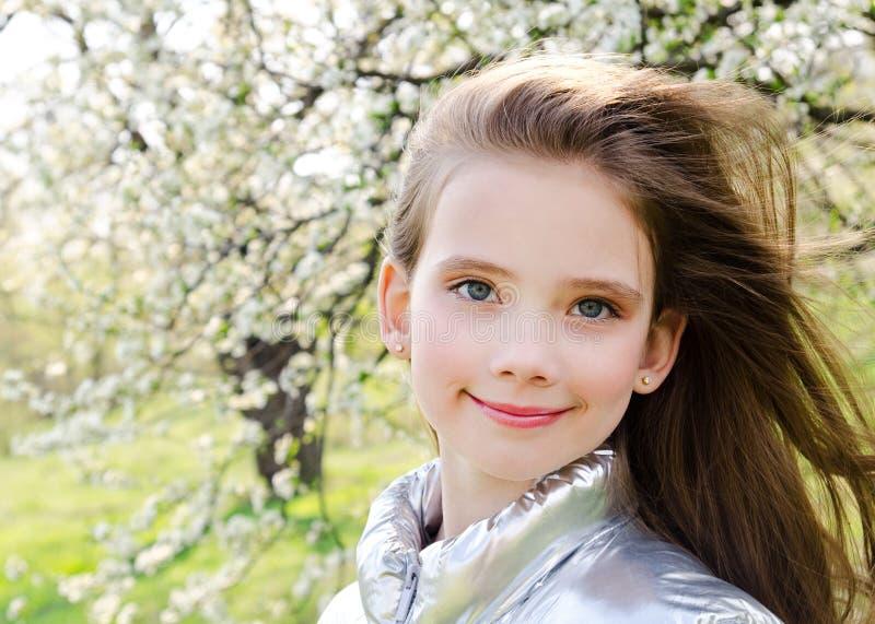 可爱的微笑的女孩孩子画象户外在春日 免版税库存图片