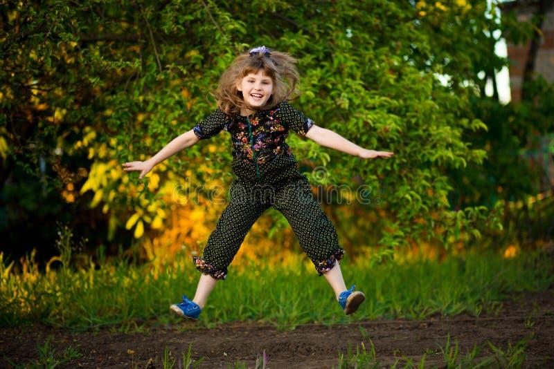 可爱的微笑的女孩画象在公园跳跃在日落 儿童愉快的秋天来 图库摄影