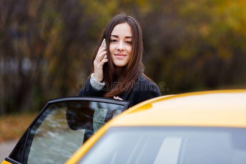 年轻可爱的微笑的妇女发表演讲关于手机在出租汽车附近 库存照片