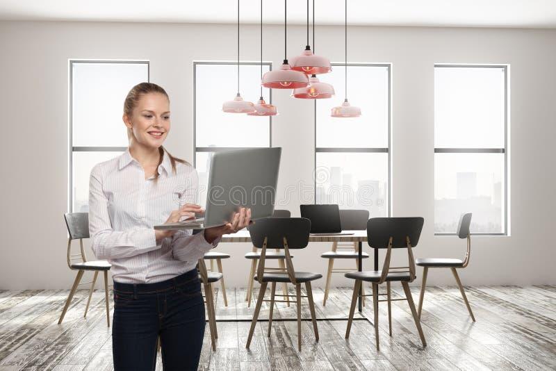 可爱的微笑的妇女在会议室 免版税图库摄影