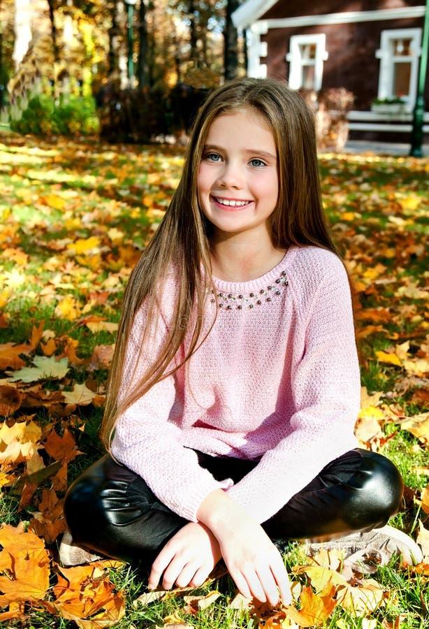 可爱的微笑的小女孩孩子秋天画象有leav的 库存照片