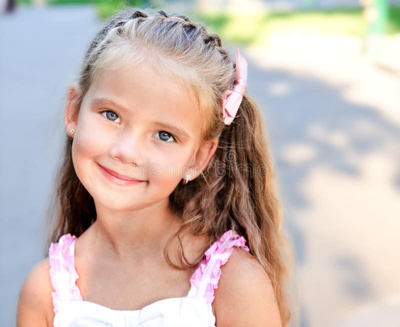 可爱的微笑的小女孩画象在公园 库存图片