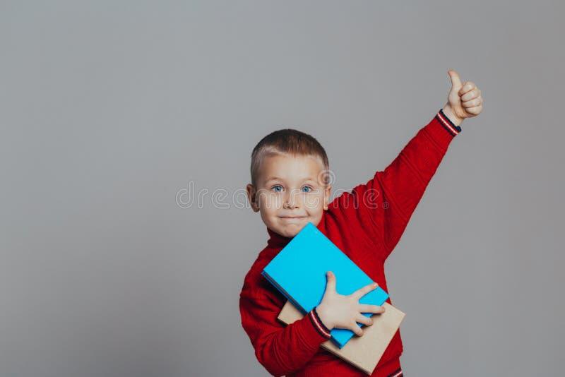 可爱的微笑的男孩画象一件红色毛线衣的有书特写镜头的 库存图片