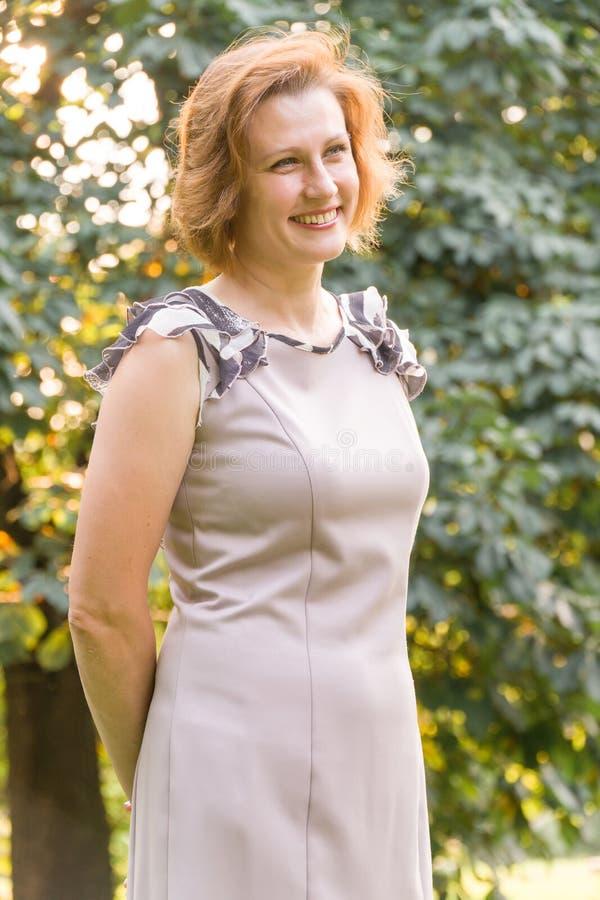可爱的微笑的白种人种族少妇画象在公园 库存照片