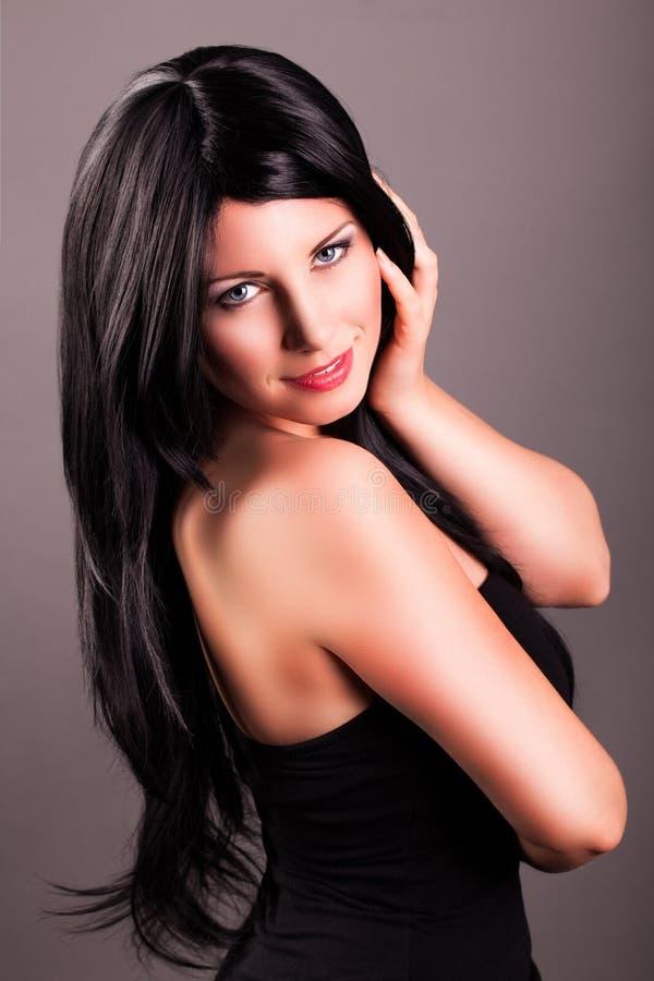 可爱的微笑的黑发妇女 免版税库存照片