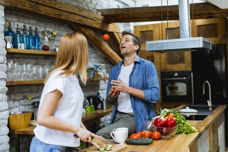 可爱的快乐的夫妇一起烹调晚餐和获得乐趣在土气厨房 免版税库存照片