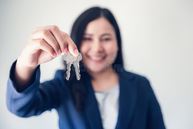 可爱的快乐的妇女特写镜头画象显示钥匙的衣服的反对白色背景,美丽女实业家 免版税库存照片
