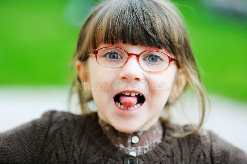 可爱的惊人的女孩她一点显示舌头 免版税库存照片