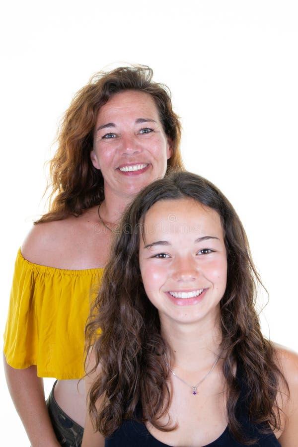 可爱的愉快的卷曲母亲和微笑十几岁的女儿 免版税库存图片
