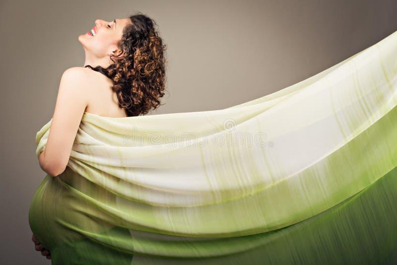 可爱的愉快的孕妇以绿色 免版税库存照片