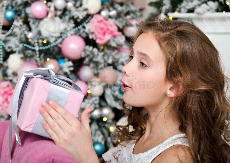 可爱的愉快的惊奇的女孩儿童藏品礼物盒画象在杉树附近的 免版税库存照片