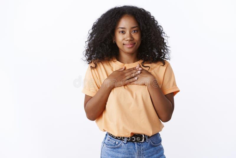 可爱的感激的有吸引力的年轻非裔美国人的女孩卷曲理发新闻棕榈胸口感恩的欣赏姿态 免版税图库摄影