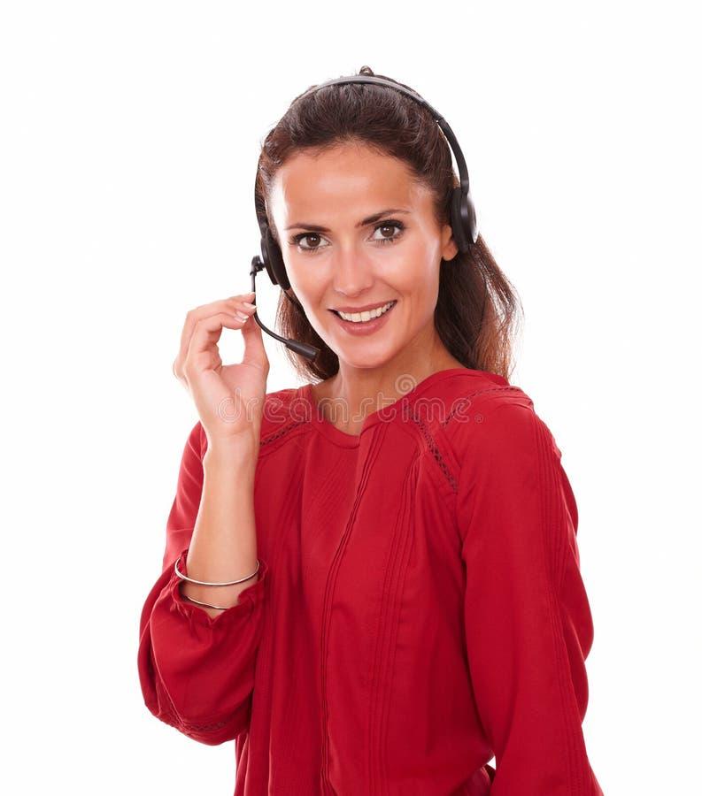 可爱的成人秘书发表演讲关于耳机 免版税图库摄影