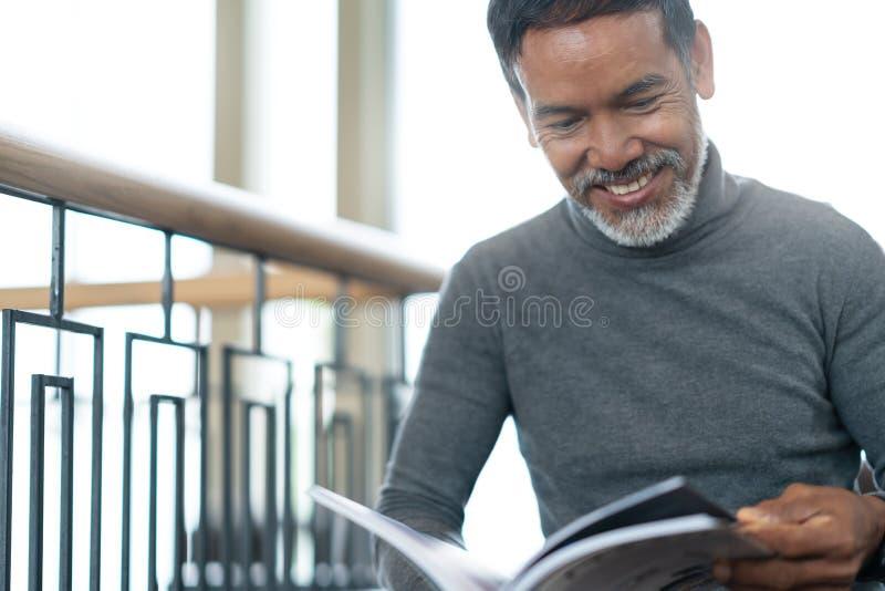 可爱的成熟亚裔人画象退休了与时髦的短的胡子开会,微笑和读杂志书 库存图片