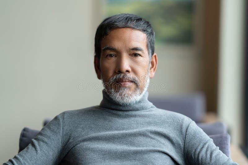 可爱的成熟亚裔人画象退休了与白色铁笔 库存照片