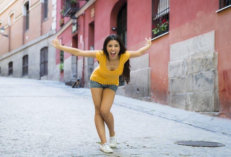 年轻可爱的拉丁妇女愉快和激动摆在现代都市欧洲城市 库存照片