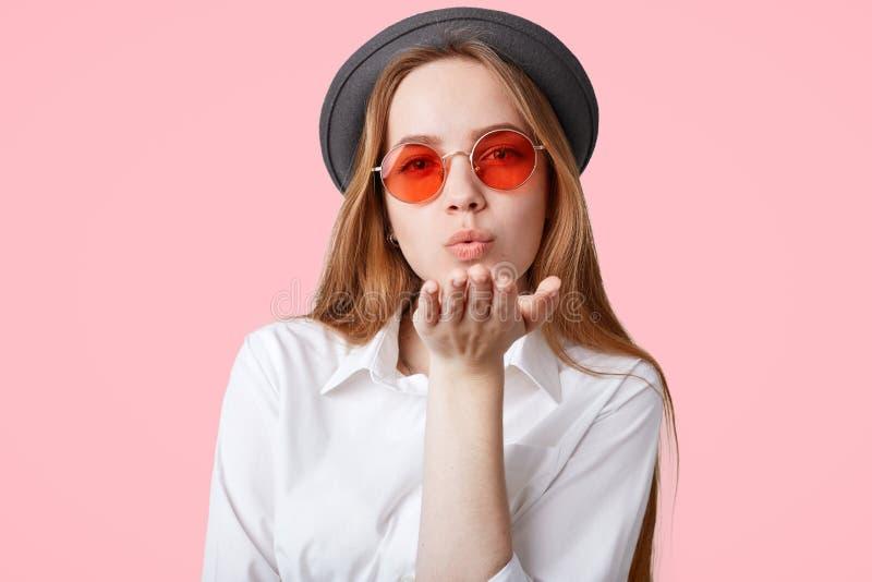可爱的时兴的行家女孩佩带时髦桃红色树荫,并且黑帽会议,送空气飞吻在照相机,摆在反对桃红色背景, e 免版税库存图片