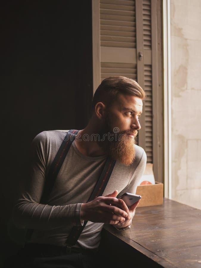 可爱的有胡子的人是在电话的传讯 免版税库存照片