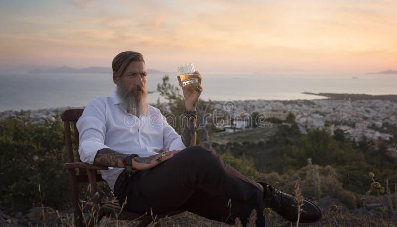 可爱的有胡子的商人坐在山和饮用的威士忌酒的椅子在日落 图库摄影