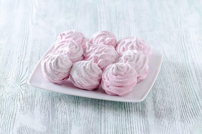 可爱的柔和的淡色彩玫瑰蛋白甜饼,和风,在木葡萄酒桌上的蛋白软糖 免版税库存照片