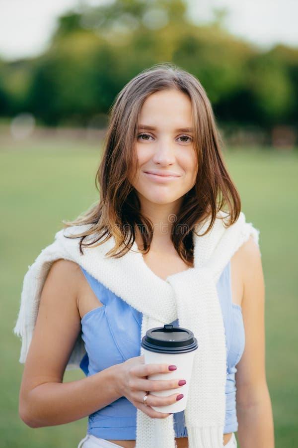 可爱的欧洲女性室外画象有吸引人的神色的,穿戴在便衣,拿着外带的咖啡,享用晶石 库存照片